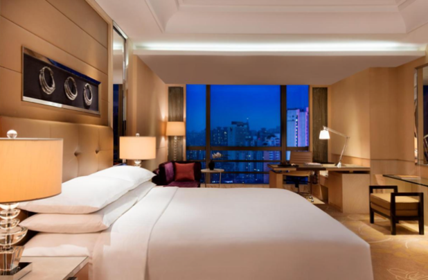 A hotel room with a large bed  Description automatically generated with medium confidence